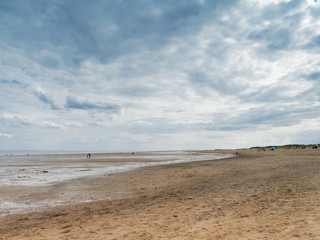 Dark clouds gather over an almost deserted beach