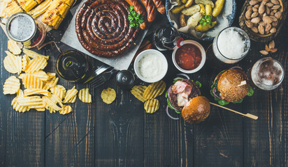 Beer and snack set. Octoberfest food frame concept. Variety of beers, grilled sausages, burgers, fried potato, corn, chips and sauces on dark wooden scorched background. Top view, copy space