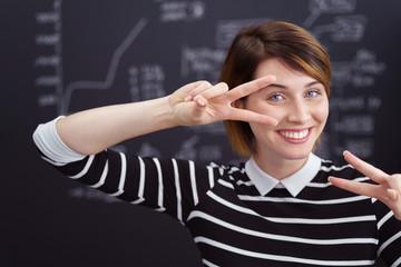 studentin zeigt victory-zeichen mit beiden händen