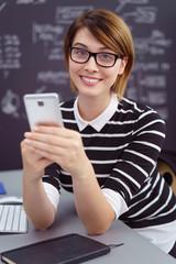 junge frau arbeitet am schreibtisch und schaut auf ihr mobiltelefon