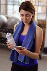 frau mit wasserflasche und handy im fitness-studio