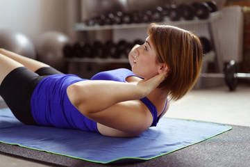 frau macht situps im fitnessstudio