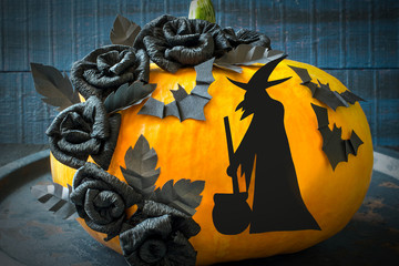 Halloween design. Black roses, the witch and bat of paper on a p