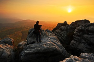 Rocky landscape with photographer during autumn. Beautiful landscape with stone. Sunset in czech national park Ceske Svycarsko. Misty evening autumn landscape. Landscape with rock hills. Evening sun.