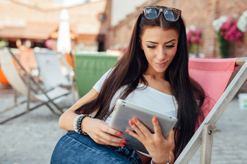 Young girl sitting on the sunbed and using tablet pc.