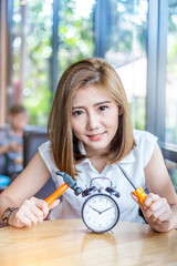 beautiful asian girl try to fixed black alarmclock