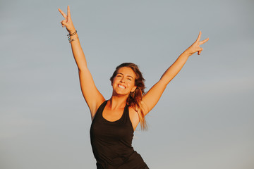 Pretty fitness woman raising arms and doing victory sign with the hands. Success concept.