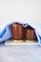 Small jars turned upside down and filled with homemade fig jam. Selective focus, copy space.