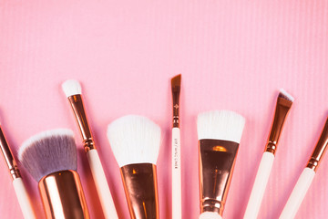 Face makeup brushes on pink.