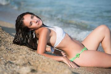 Pretty girl with long hair wear bikini, lying in the sea in profile