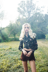 The slender blonde woman in a short brown skirt and a dark shirt in the forest. Hippie style