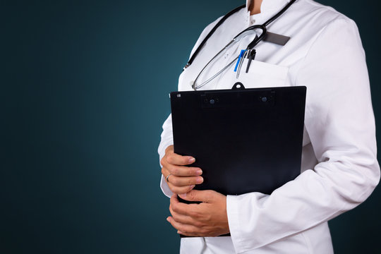 Close up of a woman doctor, holding a folder, isolated on dark-blue background.