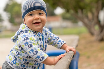 10 month old baby boy pulls up on park bench
