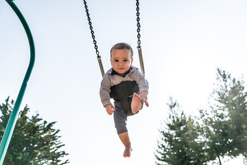 10 month old baby boy in playground swing