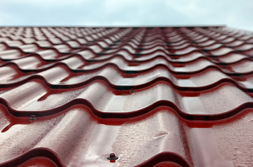 wet red metal roofing from sheet metal with droplets of rain clo