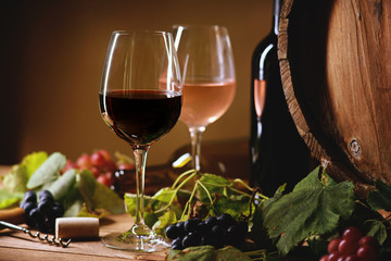 Wine bottle, glasses, grapes and barrel