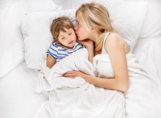 Mother and daughter whispering in bed