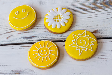 Frosted cookies with decoration. Four biscuits on wooden background. Flower and smiley face. Recipe of happy day.