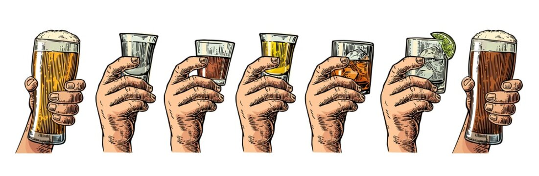 Male hand holding a glass with beer, tequila, vodka, rum, whiskey and ice cubes.