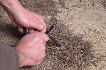 Hands using a Fire-starter tool. Survival skills and techniques