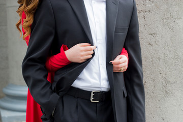 girl in red dress embracing a man in a black suit and white shirt