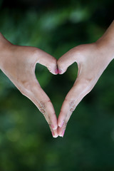 Closeup of woman hands making heart shape gesture