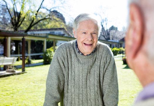 Happy retired men talking outdoor in a rehab facility garden