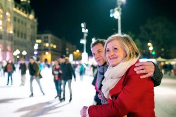 Beautiful senior couple ice skating in city centre. Winter