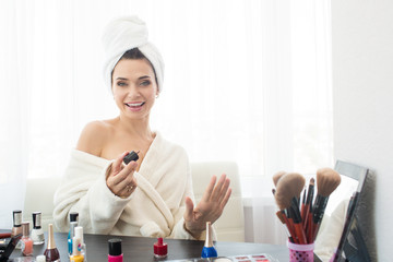 Young woman doing manicures at home.