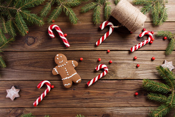 Christmas background. Gingerbread man and Christmas cane on a wooden background