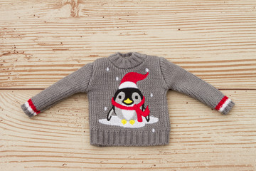 Gray and Red Penguin Christmas Sweater on a Weather Wood Backgro