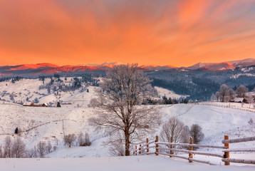 Fantastic winter mountain landscape with snow and fiery sky