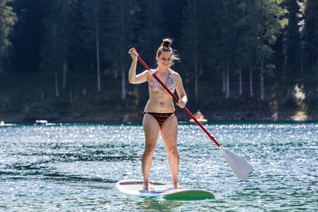 Girl on a paddleboard on the Caumasee in Switzerland