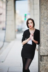 Young beautiful girl with bright lipstick in a black cardigan and short skirt standing outside leaning on  pillar of the old building  Petersburg.