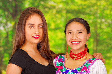 Two beautiful young women posing for camera, one wearing traditional andean clothing, the other in casual clothes, both smiling, park background