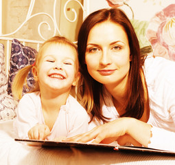 portrait of mother and daughter laying in bed reading book smiling