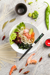 Traditional Japanese noodle soup, meat, vegetables, red pepper in a white plate with chopsticks. On a wooden background