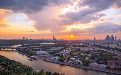 Panoramic view of sunset above Moscow city and cloud reflections in river with traveling boats