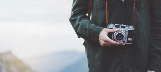 Hipster girl with backpack on peak of foggy mountain, tourist traveler photographer taking pictures of amazing landscape on vintage photo camera on background valley view mockup sun flare
