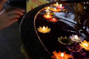 Lotus flower candle lighting and floating in the water, faith and belief concept.