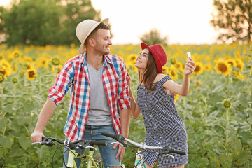 Young couple on bicycles taking photo in field