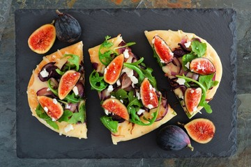 Autumn flat bread pizza with figs, arugula, and goat cheese, overhead scene on slate background