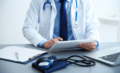 Clipboard with cardiogram and tonometer on doctor workplace