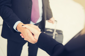 Businessman making handshake with a businesswoman while holding