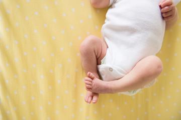 newborn baby on yellow blanket