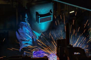 Worker welding automotive part in factory