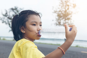 Cute girl is drinking water from plastic bottle. Clean water wil