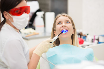 The reception was at the female dentist. Doctor examines the oral cavity on tooth decay. Caries protection. Tooth decay treatment. Dentist working with dental polymerization lamp in oral cavity