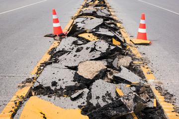 cracked asphalt road with marking lines and  orange-white stripe safty cones