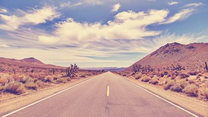 Vintage toned desert road, travel concept.